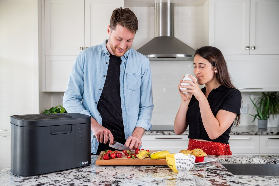 Couple cutting fruit next to a Tero food waste recycler.