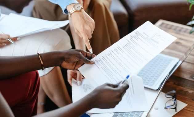 multiethnic businesswomen checking information in documents