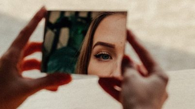 woman in makeup looking in mirror in street