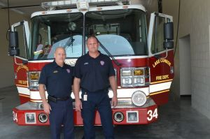 Lt. J. Hall and Firefighter J Busa standing in the equipment bay of LCFD Station 34.