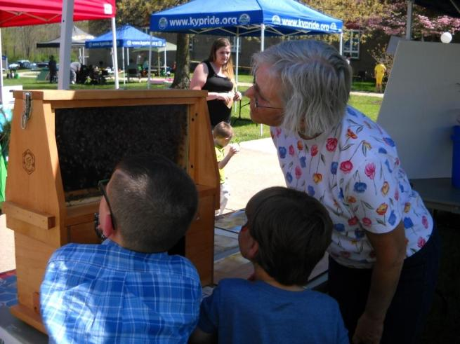 LCBA member Kathy Mantle watches the bees in the observation hive, along with two young visitors to the SCC Earth Day event. Can they find the Queen? She's in there somewhere, marked with a green dot, along with her worker bee attendants.