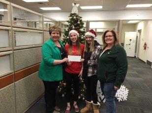 Staff at the TD Bank present a cheque to the Santa's Elves Program