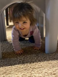 Crawling under the play table.