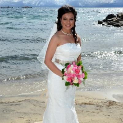 bride white dress pink bouquet on beach