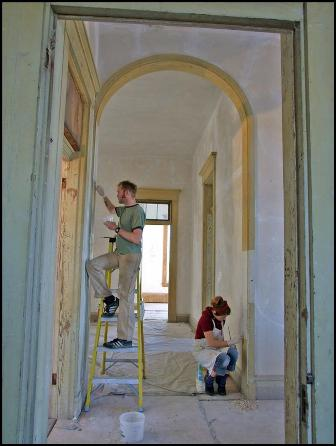 Removing yellowed original varnish and cleaning upstairs woodwork to prepare for consolidation of remaining original paint layers