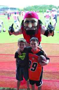 Zachary Wood, left, and Giovanni Irizarry of the Pasco Police Athletic League football team the Wesley Chapel Bulls, pose with the Tampa Bay Buccaneers mascot during a visit to a preseason training session with the professional team. The event included autographs and some tips from some of the veteran players. (Courtesy of Mary Guyer)