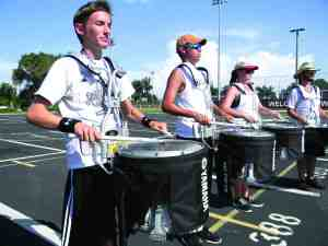 The Wiregrass Ranch High School marching band's drum line practices after school with players like, from left, Alex Dabrow, Robert Rodriguez, Ashleigh Hans and Sam Ryan. The line is raising $25,000, so that they can keep playing after marching season ends in November. (Michael Hinman/Staff Photo)