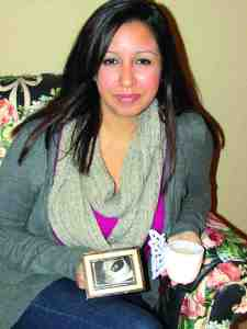 Reina Flores-Robinson says that despite the support of her husband, family and friends, going through a miscarriage is 'one of the loneliest feelings.' She's holding a candle that she and her husband plan to light on the anniversary of their child's due date each year, and a sonogram picture of the baby. (B.C. Manion/Staff Photo)