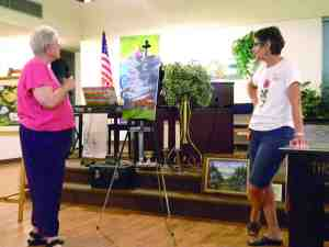 Artist Gainor Roberts, left, offers a critique of a painting by Zephyrhills Art Club president Joyce Owens. (Kathy Steele/Staff Photo)