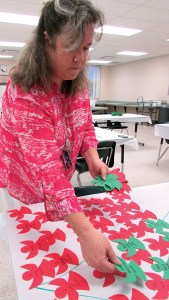 Marty Pekarek lays out angels for Centennial Middle School staff members to pick up, as the school gears up to brighten the holidays for students in need at their school. (B.C. Manion/Staff Photos)