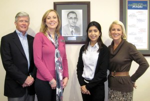 Tim Baldwin and Terri Gude, left, flank the portrait of Joe Herrmann, one of founders of the San Antonio Citizens Federal Credit Union. Carolina Rodriguez and Andy Kinross, are on the other side of the portrait. Baldwin, president, and Gude, vice president, have worked at the credit union the longest. Kinross and Rodriguez are the two newest members on the credit union's 40-member staff. (B.C. Manion/Staff Photo)