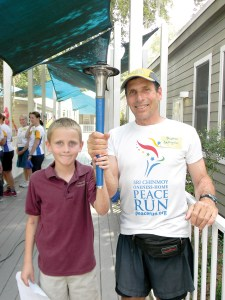 Learning Gate fifth-grader J. B. Montague, holds the relay torch with Andran DeAngelo, captain of the relay team for the Sri Chinmoy Oneness-Peach Run.