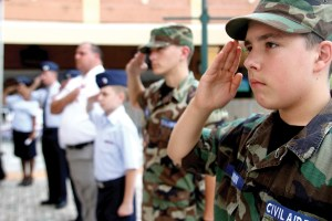 Gabriel Quinn, a cadet with the Wesley Chapel Cadet Squadron of the Civil Air Patrol, and others, salute, while Eric Johnson sings 'The Star-Spangled Banner.'