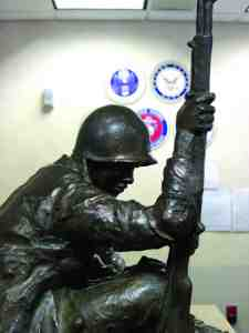This statue of a soldier in the foreground and the emblems of the various armed services in the background are symbolic of the sacrifices made by the men and women at the Baldomero Lopez State Veterans Nursing Home in service to the nation.