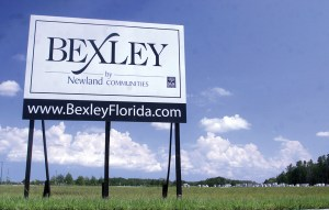 A large sign advertising future construction of the planned master-community of Bexley South seeks to catch the attention of passing motorists on State Road 54.