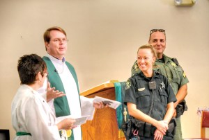 Pastor Scott Lindner presents Pasco County Sheriff's Deputy Sarah Walker and Sgt. Sam Pepenella to the congregation at the end of the service. They are assigned to District 2, which includes Wesley Chapel, Lutz and Land O'Lakes. (Richard K. Riley/Photos)