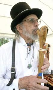 Flute maker Utah Farris, of Lake Wales, sounds a long flute that he carved and ornamented with bird-like creatures. He performed and sold handmade flutes at the two-day Silverhawk Native American Flute Gathering at the Withlacoochee River Park in Dade City. (Fred Bellet/Photos)