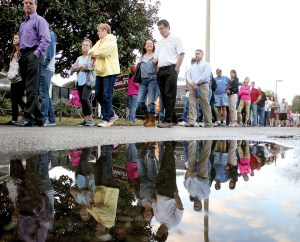 At Precinct 70, a long line forms and is reflected in a puddle of water left behind by the irrigation system early Tuesday morning.