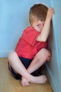Boy in a corner looking afraid.