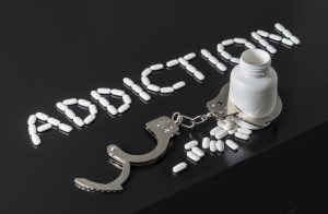 "The word ""Addiction"" spelled with pills with a bottle and handcuffs beneath it."