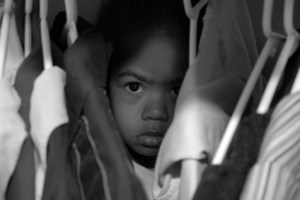 A young girl hiding between clothes hanging.