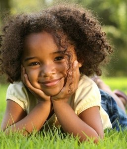 A little girl smiling, lying in the grass