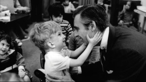 a small boy, hugging Mr. Rogers