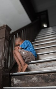 a boy, looking distraught, sitting on the stairs