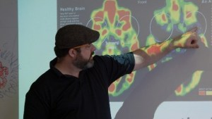 a man teaching with a photo of brain mapping