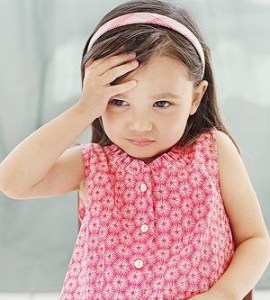 a young girl holding her head as though she has pain there