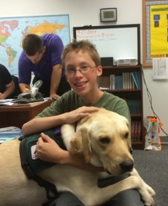 student hugging service dog