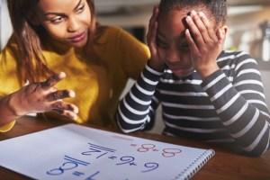 mother helping child finish homework