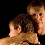 man hugging son around neck