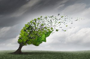 Psychological trouble and mental health adversity crisis as a tree shaped as a human head being torn or stressed by strong winds as a psychiatry or psychology icon