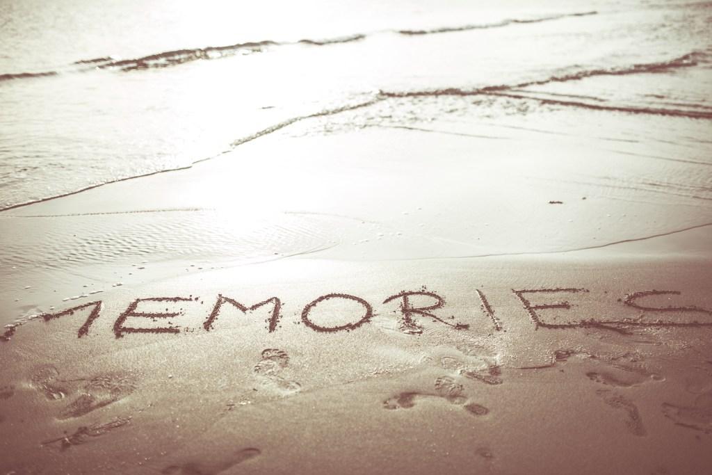 Word memories written in the sand Concept of fading memories.