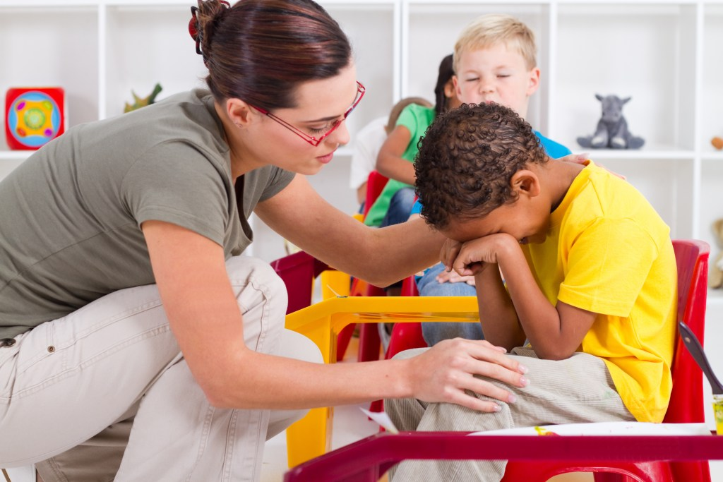 teacher comforting crying preschool boy in classroom