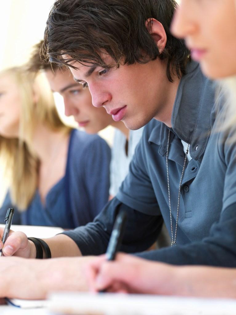 Teen boy taking notes