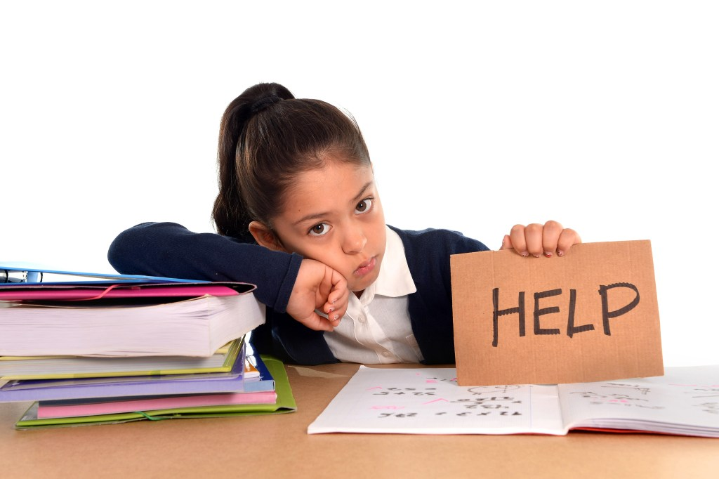 female latin child studying on desk asking for help in stress with a tired face expression