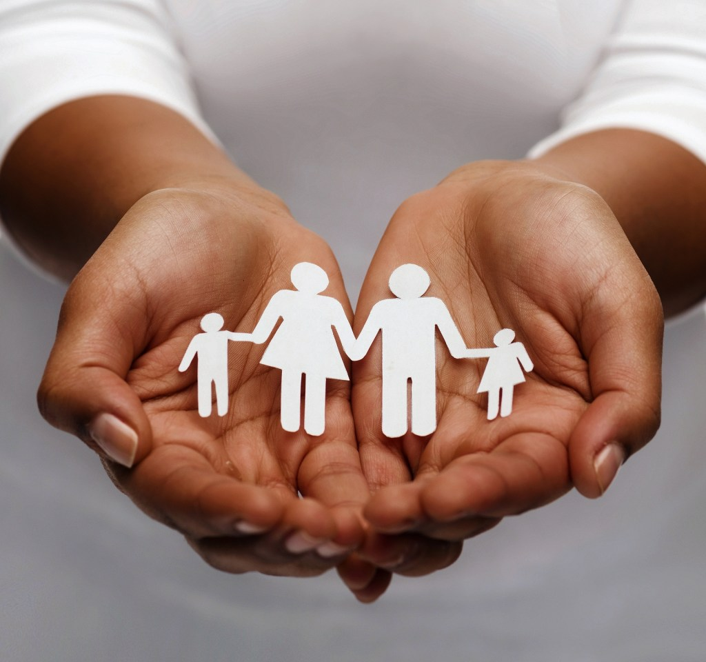 closeup of womans cupped hands showing paper man family