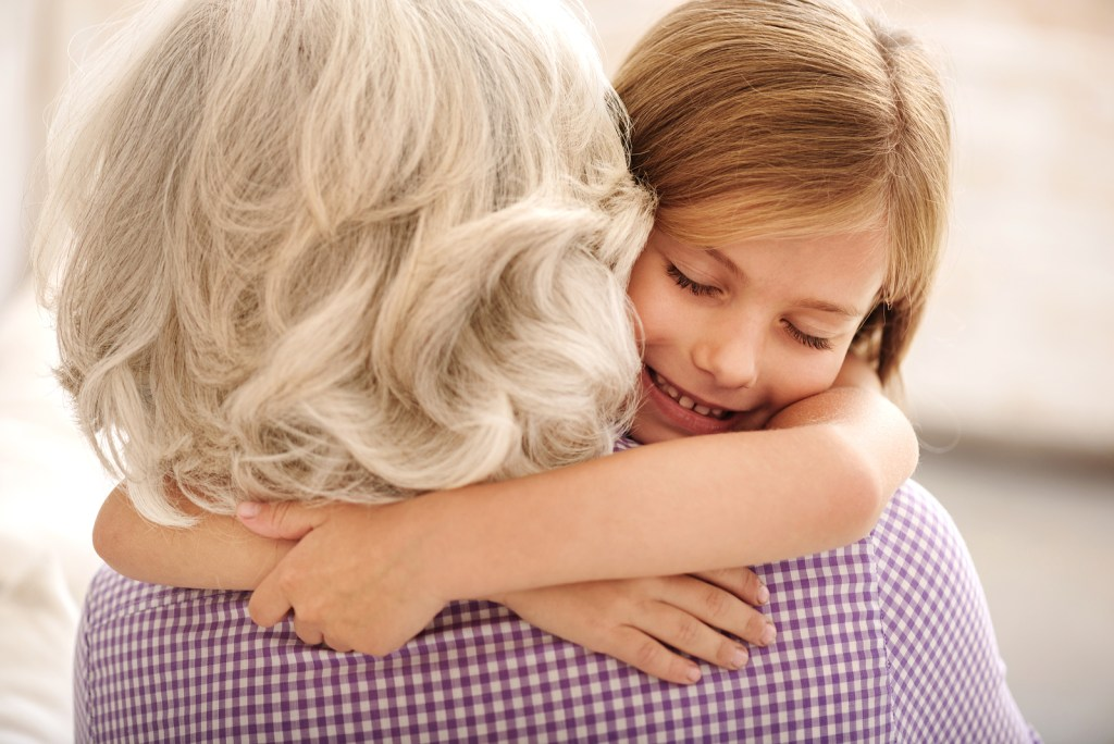 granddaughter and grandmother hugging. Girl is smiling with closed eyes