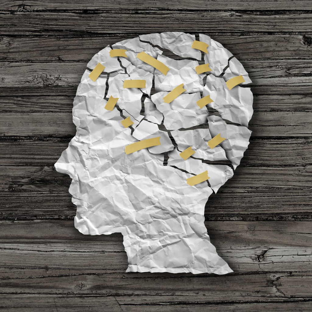 therapy and mental health treatment concept as a sheet of torn crumpled white paper taped together shaped as a side profile of a human face on wood, psychological help concept.