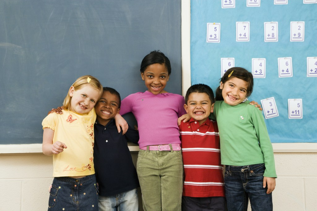 Group of diverse young students standing together in classroom.