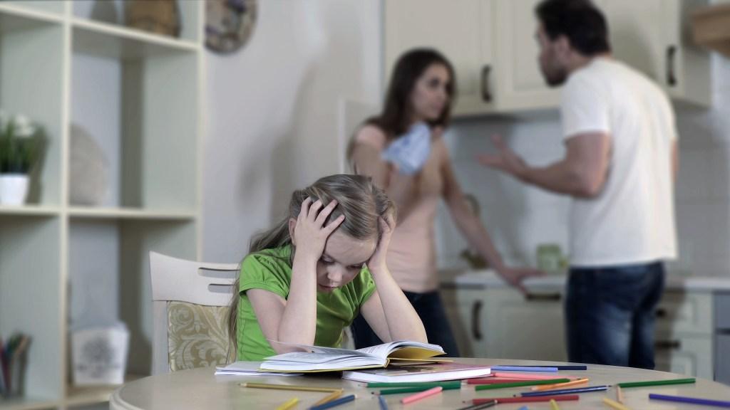 Upset child listening divorcing parents fight
