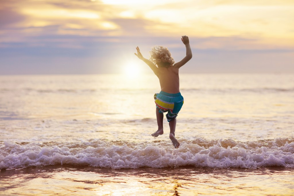 Child playing on ocean beach, jumping in the waves at sunset. Sea vacation for kids.