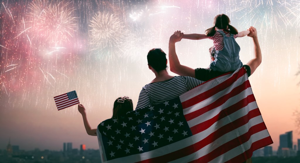 Patriotic holiday. Happy family, with American flag. USA celebrates 4th of July.