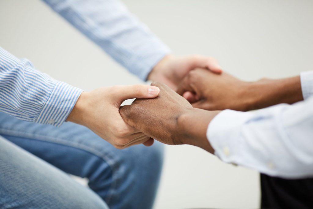 Two people holding hands heartily during therapy session