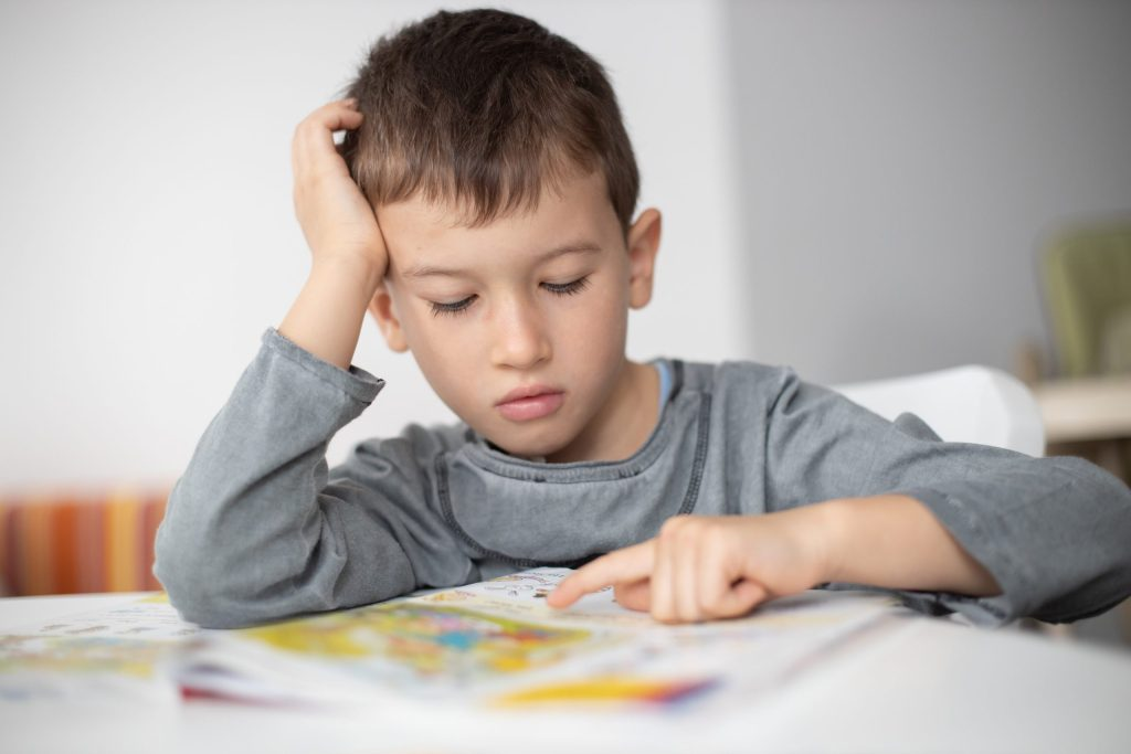 young boy struggling with his reading