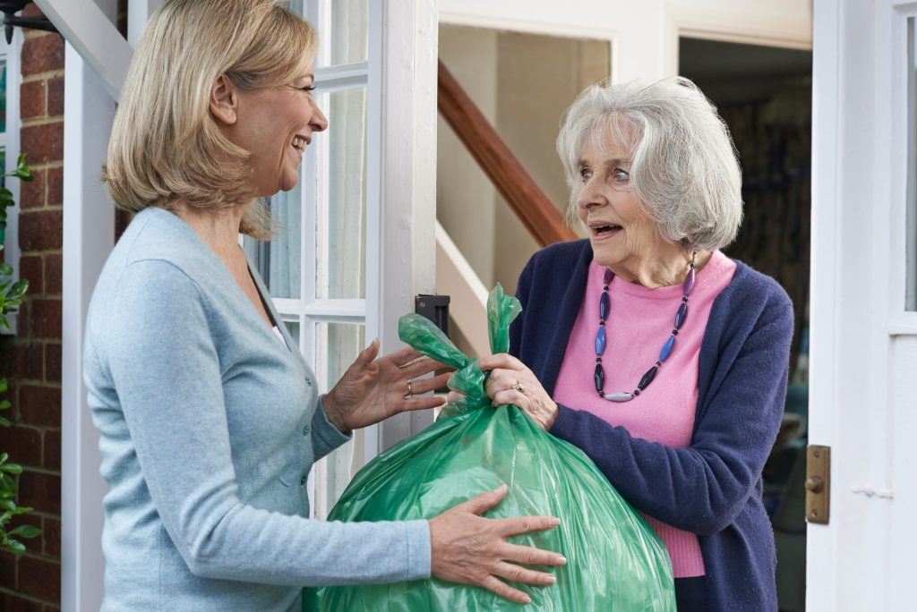 Woman Taking Out Trash For Elderly Neighbor
