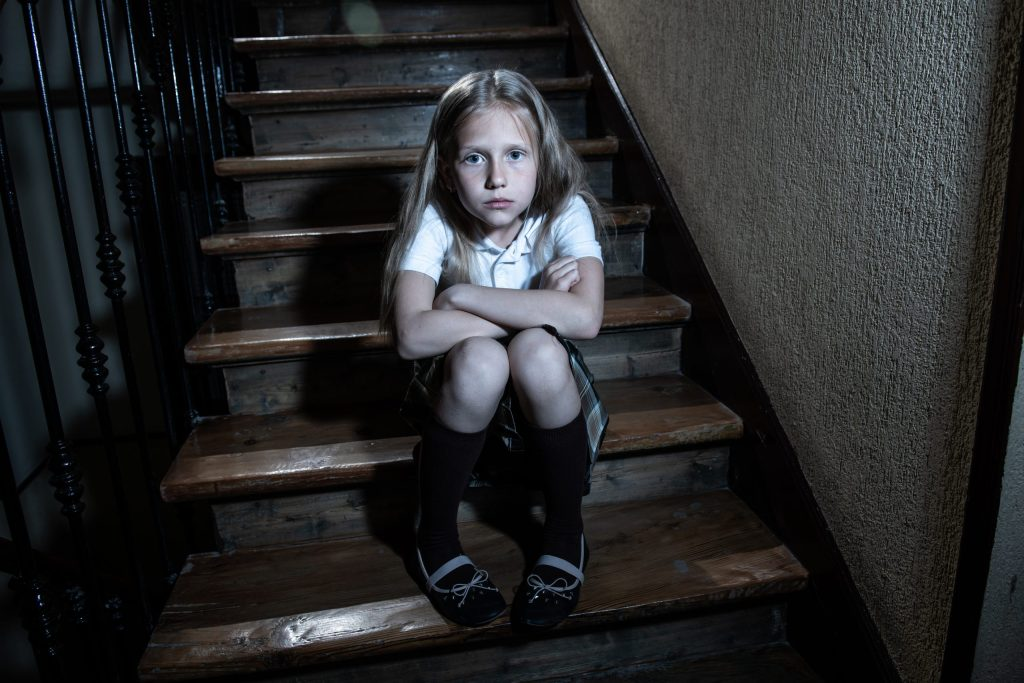 Sad, depressed, unhappy schoolgirl feeling lonely and hopeless sitting on stairs with dark light.