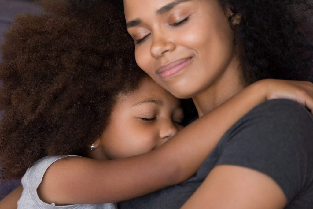 Loving  black mother hugs cute daughter to feel connection and safety.